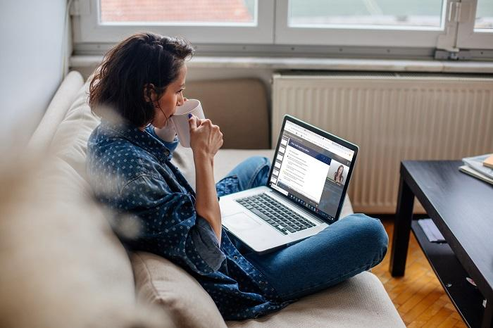 a woman looks at the Becker site on a couch on a laptop while drinking from a mug